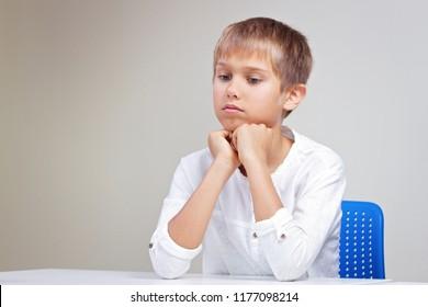 Thinking schoolchild sitting at empty white desk
