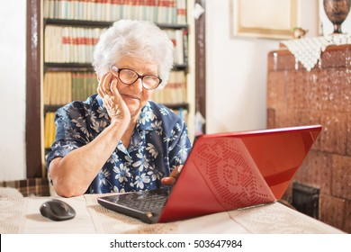Thinking senior woman exploring laptop functions. Technology, oldness and lifestyle concept.