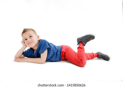 Thinking smiling little boy lying down on floor and looking up.  Isolated on white background