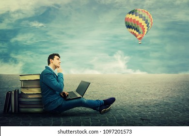 Thinking student sitting on a pavement floor lean on a pile of books, using laptop and a hot air balloon flying. Modern education concept. New technology replace old methods in educational process.
