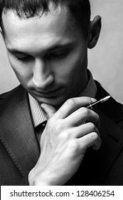 Thinking successful businessman with pen. Face close up