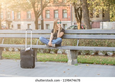 thinking tourist woman, sitting on the bench in the park,  luggage on the street