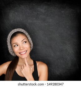Thinking woman by blackboard. Multiracial hipster university college student pensive and contemplating looking up to the at empty blank copy space on chalkboard black background. Asian Caucasian, 20s.