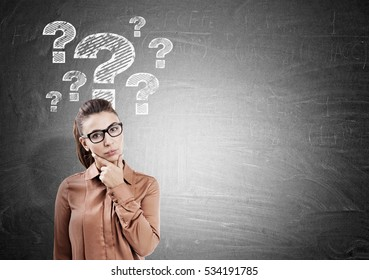Thinking woman in glasses with her fingers on the chin is standing near a blackboard with question marks. Mock up