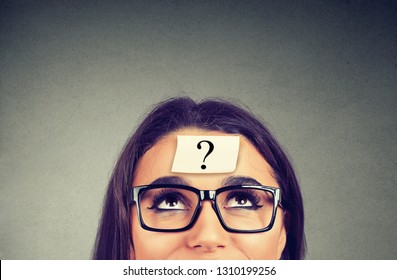thinking woman in glasses with question mark looking up on gray wall background