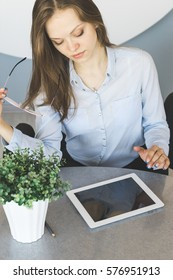 Thinking woman with glasses and in suit looking something in tablet pc on the table