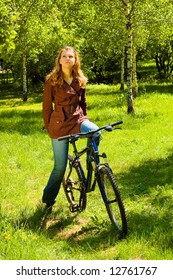 Thinking woman on bicycle in the spring forest