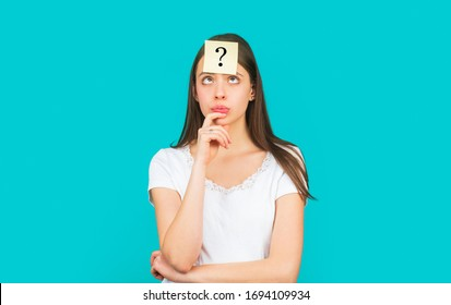 Thinking woman with question mark looking up. Doubtful girl asking questions to himself. Paper notes with question marks. Confused female thinking with question mark on sticky note on forehead.