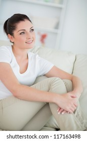 Thinking woman sitting on the couch in the living room and smiling