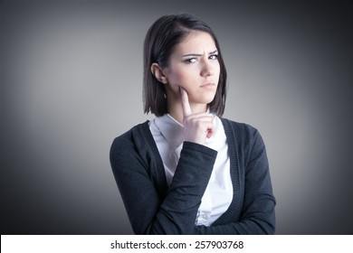 Thinking woman standing pensive contemplating looking skeptic.Thinking business woman expressing anger,confusion and distrust.Young brunette looking curious,evaluating something
