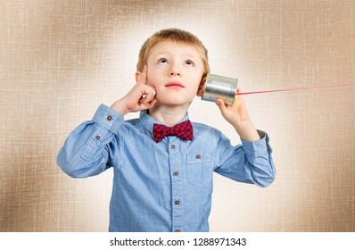 thinking young boy is  listening with tin can telephone