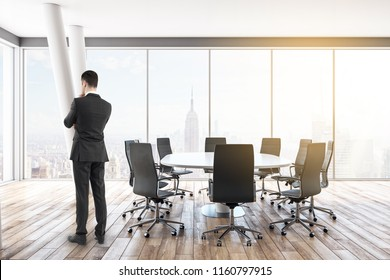 Thinking young businessmen standing in modern meeting room interior with panoramic city view. Career, job and occupation concept.