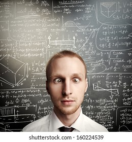 thinking young man against desk with formulas