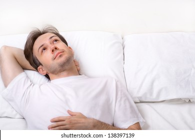 Thinking young man lying on bed and looking away
