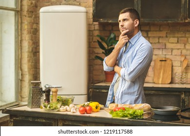 Thinking young man preparing delicious and healthy food in the home kitchen on a sunny day.