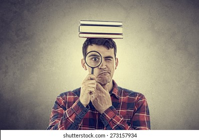 Thinking Young man student holding magnifying glass and a  stack of books on head isolated over grey background.Curious young student man holding books with a magnifying glass.