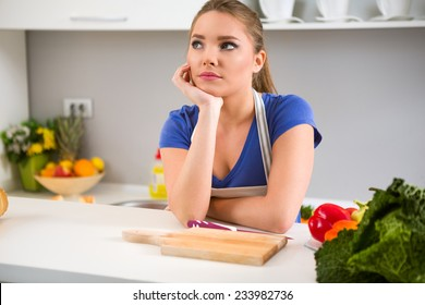 thinking young woman wondering what to cook in kitchen