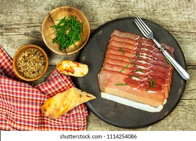 Thinly sliced German black forest ham with sliced ciabatta bread. Sliced and smoked ham with schwarzwald ham or prosciutto. Traditional German food