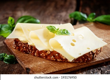 Thinly sliced gouda cheese on wholewheat bread garnished with fresh basil served on a wooden board, close up view