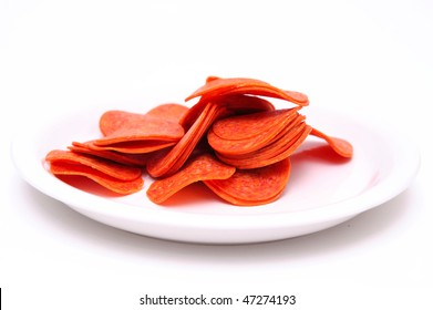 Thinly sliced pepperoni piled on a white plate ready to be placed on a pizza or sandwich
