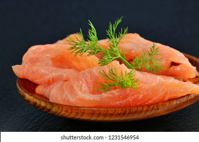 Thinly sliced smoked salmon fillet, on plate over black slate platter