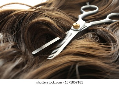 Thinning scissors on brown wavy hair, closeup. Hairdresser service