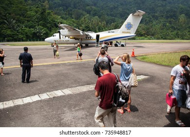 THIOMAN ISLAND, MALAYSIA - AUGUST 6,2012: Tourists go to the plane for their flight through the airfield