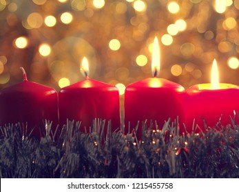 Third Advent candle burning, Seasonal background with red Advent candles and golden Christmas decoration