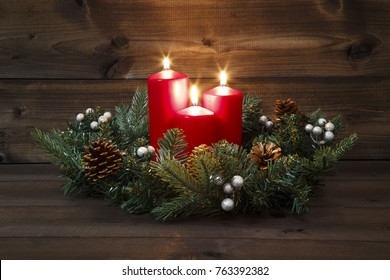Third Advent - Decorated Advent wreath with three red burning candles on a wooden background