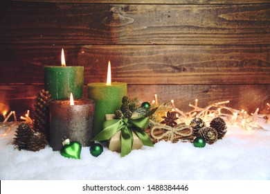 Third Advent. Green christmas candles in snow on rustic wooden background