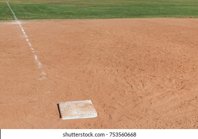 Third base showing baseline and outfield in blurred background. Room for text.