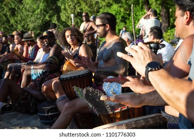 Third Beach, Downtown Vancouver, British Columbia, Canada - May 22, 2018: People having fun at a Drum Circle Event during a vibrant sunset.