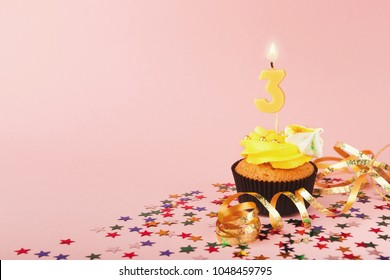 Third birthday cupcake with candle and sprinkles on pink background. Card mockup, copy space. Birthday, party, holiday concept