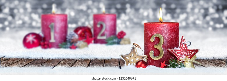third sunday of advent red candle with golden metal number one on wooden planks in snow front of silver panorama bokeh background