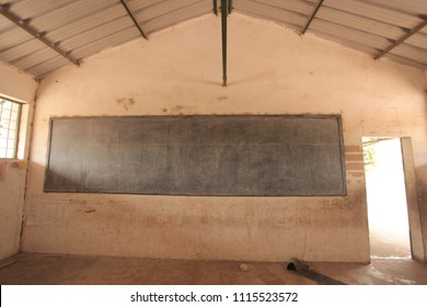 third world education - inside of a poor african school classroom, with dirty walls, old school dusty wooden blackbord, with bright open door , in the Gambia, Africa