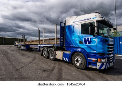 Thirsk, North Yorkshire / UK - April 23 2018: WS Transportation Scania Semi Truck Abnormal Load carrying Steel Girders on an Extendable Trailer with Storm clouds overhead and Sunlight on the Vehicle.