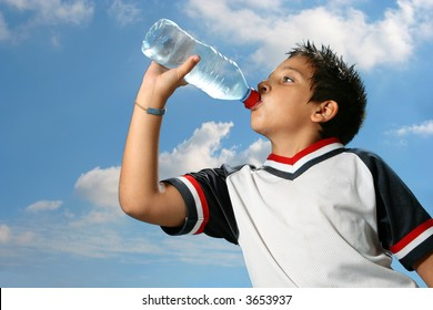 Thirsty boy drinking fresh water outdoors wearing sport clothes