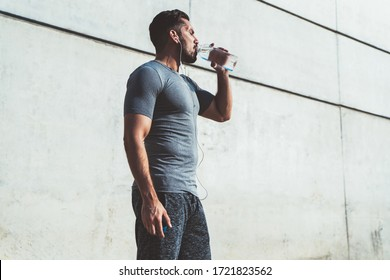 Thirsty caucasian male jogger in active wear and earphones holding water bottle get refreshment after jogging,serious man in white t-shirt drinking after having training workout on stadium keeping fit
