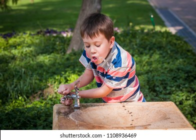 Thirsty cute little Caucasian boy drinking water from a street drinking fountain. Child drinking from a water fountain. Thirst and dehydration stock image. Dry summer heat, sunstroke, overheat.