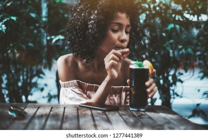 A thirsty dazzling curly biracial female is holding the glass of a tasty cold ice tea or a mint cocktail and drinking it using a straw while sitting alone in a street bar on a warm summer day