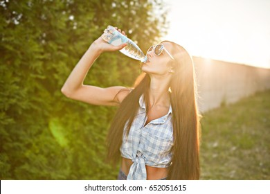 Thirsty girl with long hair is drinking water outdoors