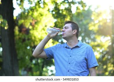 Thirsty man drinking bottled watter