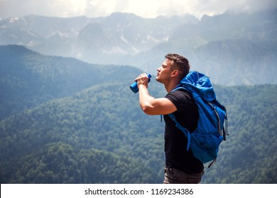 Thirsty mountaineer drinks water on the mountain