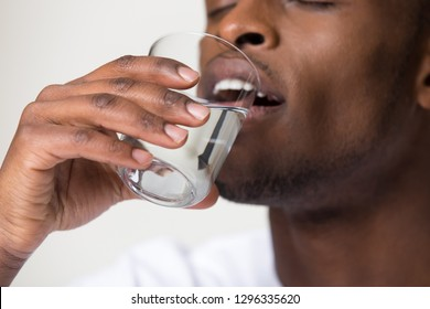 Thirsty young african man holding glass drinking water for body health isolated on white studio background, black guy feel dehydrated, healthy lifestyle, thirst and hydration concept, close up view