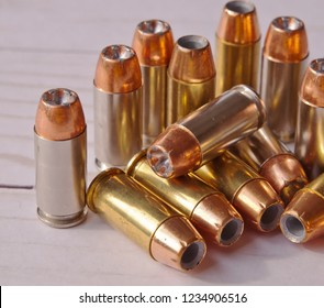 Thirteen different 40 caliber hollow point bullets together on a white wooden background. The bullets have silver cases on several and brass on the others