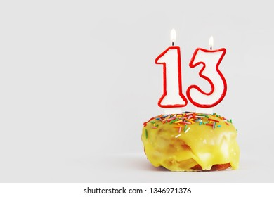 Thirteen  years anniversary. Birthday cupcake with white burning candles with red border in the form of number Thirteen. Light gray background with copy space