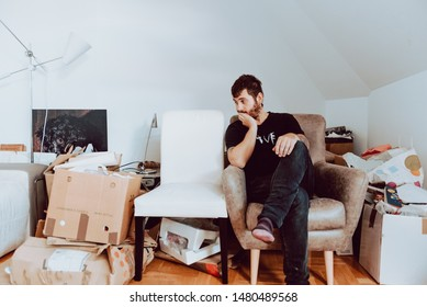 Thirties man with a beard and piercings, lazy and tired, is sitting in a chair watching the moving house boxes while taking a break.