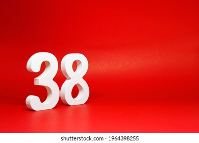 Thirty Eight ( 38 ) white number wooden Isolated Red Background with Copy Space - New promotion 38% Percentage  Business finance Concept