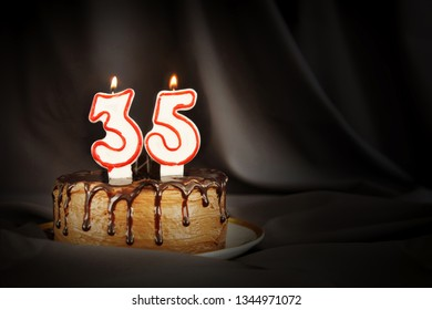 Thirty five years anniversary. Birthday chocolate cake with white burning candles in the form of number Thirty five. Dark background with black cloth