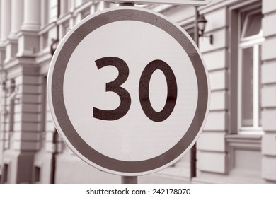 Thirty Kilometer Per Hour Speed Limit Sign in Urban Setting in Black and White Sepia Tone